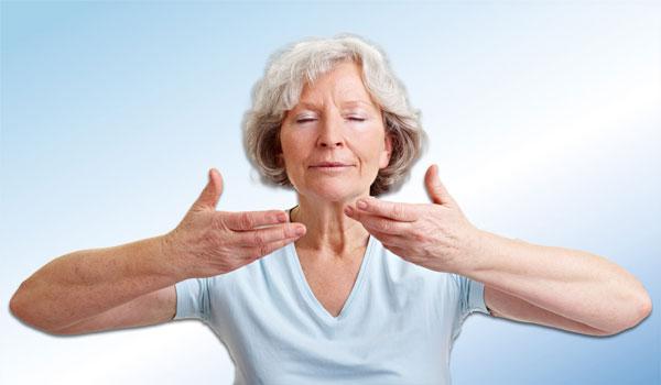 Пожилая женщина делает дыхательные упражнения