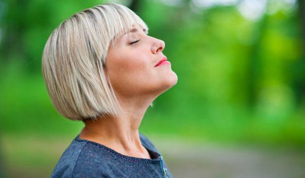 Женщина вдыхает свежий воздух