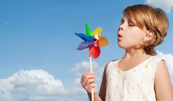 Девочка дует ветрячек